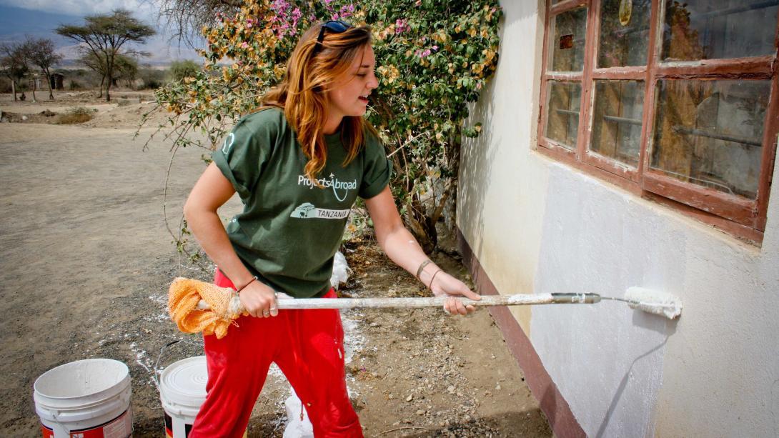 Voluntaria de Construcción pintando el muro de un aula en Tanzania.
